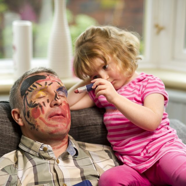 little girl has fun with a sleeping father